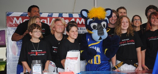 Boomer the Panther pauses with members of Fishers Boxing and Brazilian Jiu-Jitsu for a picture by visitors at the Fishers Freedom Festival. Boomer the Panther visited various booths at the Fishers Freedom Festival.