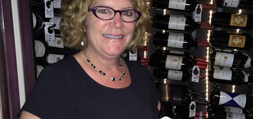 Jan Bugher holds a bottle of wine from Peterson's. (Photo by James Feichtner)