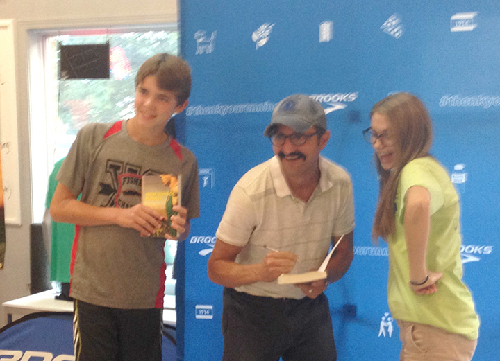 Zach Steinmetz, left, of Fishers, and Katie Darragh, right, of Lawrence attended a book signing with Bill Kenley. (Photo by Mark Ambrogi)