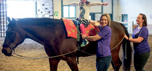 Therapy horse Rocky helps physical therapist assistant Jen Grillo work with Catalina Joyce during a physical therapy session along with horse handler Sarah Myers. (Photo by D. Todd Moore)
