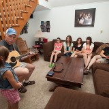 Mike Delph plays guitar with his daughter, Lilly, by his side. The rest of the family looks on in their Carmel home. (Photo by Sam Aasen)