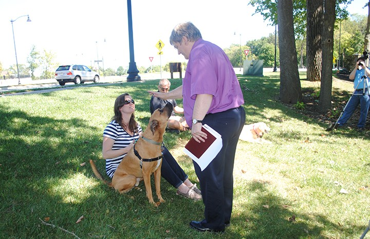 Pastor David Hewitt blesses an area dog during King of Glory Lutheran Church's pet blessing service. (Photo by Mark Ambrogi)