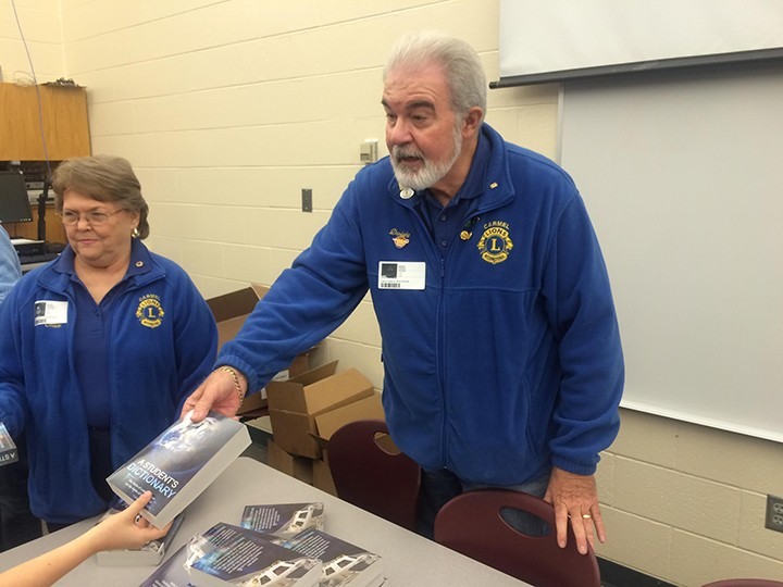Lions Club member Dwight Gossett and wife Alice hand out dictionaries. (Photo by Mark Ambrogi)