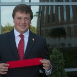 """Dustin Meeks carries a part of the ribbon that was cut during the ribbon cutting ceremony for Botsford/Swinford Hall at Ball State University. Students who live at Botsford/Swinford call the hall """"Bot-Swin."""". (Photo by Jason Conerly)"""