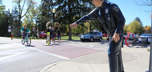 Pedestrians on the Monon Trail cross Main Street near a police officer sculpture. (Photo by Ann Marie Shambaugh)