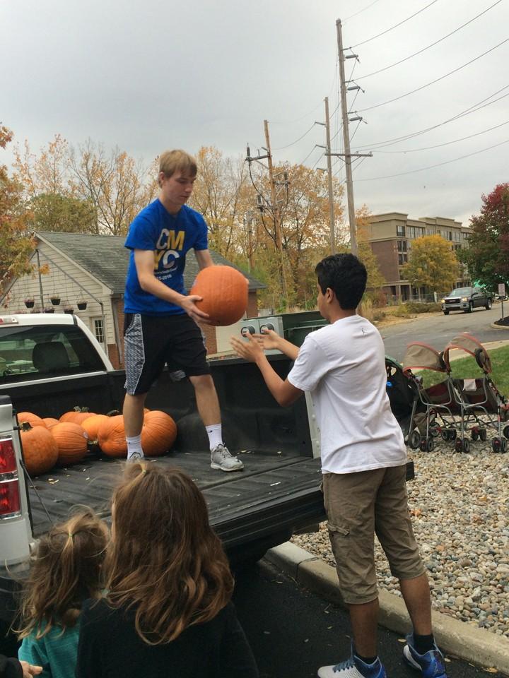 Jackson Holferty unloads pumpkins. (Photo by Kayla Nakeeb)