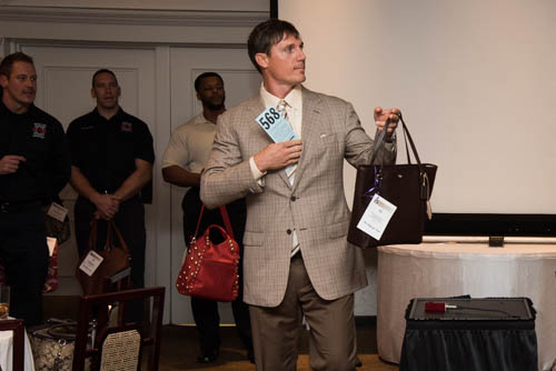 Retired Colts longsnapper Justin Snow models a purse and bids at the same time at a past Handbags for Hope event. (submitted photo)