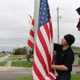 HSE grad and Army veteran Mark Isbell raises a flag at the American Legion in Lapel. Isbell dedicates his time to ensuring local, worn out American flags are retired, replaced with new flags and properly displayed. (Photo by James Feichtner)