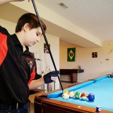 Fishers High School student Matthew Webber performs one of his billiards trick shots at his home in Fishers. (Photo by Feel Good Now, Inc.)