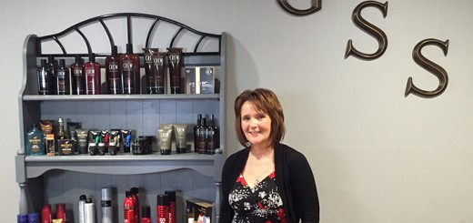 Penny Foster stands next to the merchandise in her new salon, Grand Style Station (Photo by Anna Skinner)