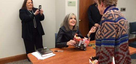 Hank Phillipi Ryan signs a book for a fan, as her sister, Nancy Landman of Carmel, takes a photo. (Photo by Mark Ambrogi)