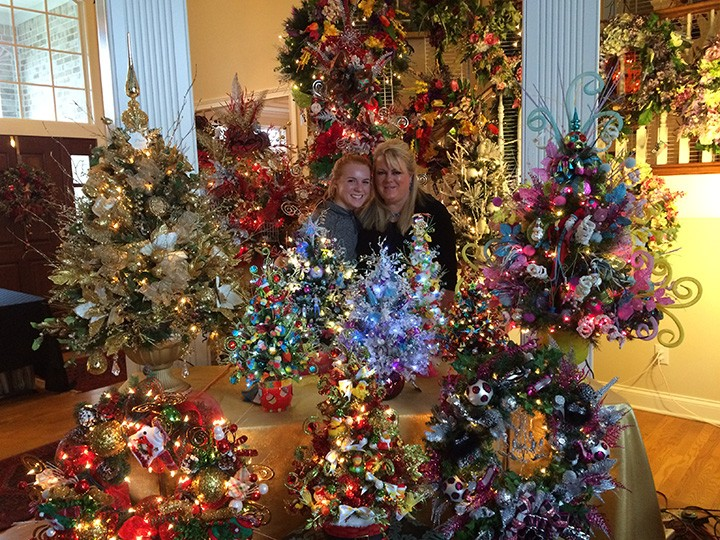 Darian Dunn, left, with her mother, Dana Dunn, in front of Dunn's designs in her Carmel home. Darian helps by tying small bows for the designs. (Photo by Mark Ambrogi)