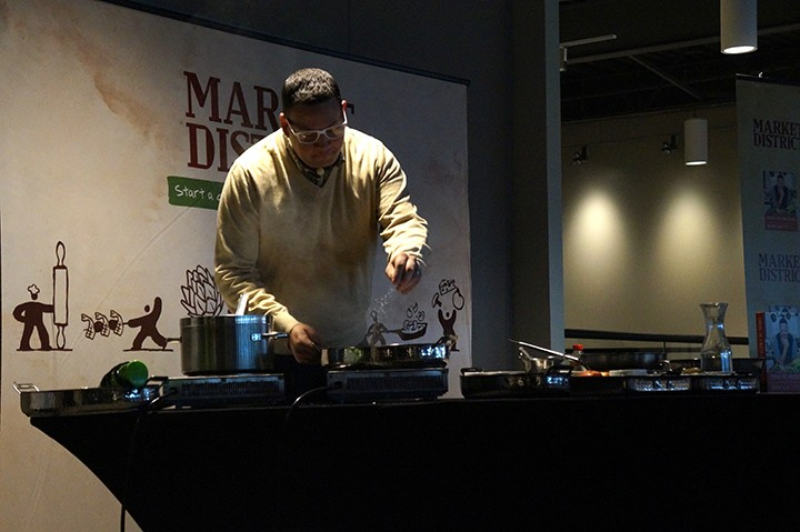 Chef Graham Elliot prepares a dish from his cookbook at Market District. (Photo by Audrey Bailey)