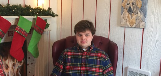 Jacob Stoesz takes a break next to his painting of a Great Pyranees in the Santa House. (submitted photo)