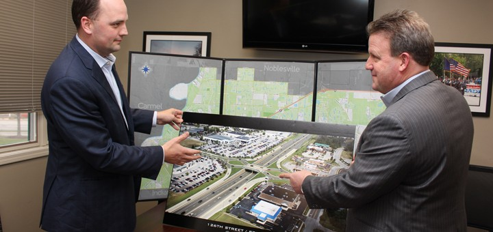 Fishers Mayor Scott Fadness, left, and Hamilton County Commissioner Mark Heirbrandt look over a proposed rendering of a roundabout at the intersection of State Road 37 and 126th Street. (Photo by James Feichtner)