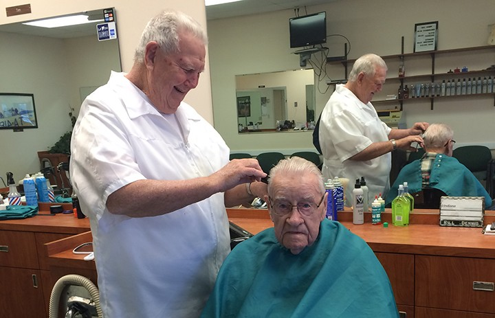 Bill Dennis gives Bill Clark a haircut. Clark comes into the shop every three weeks. (Photo by Mark Ambrogi)