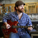 Jer Lile plays a guitar at his shop. The CHS grad recently completed a documentary that answers several questions about his late uncle, who was also a musician. (Photo by Feel Good Now)