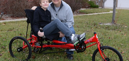 Fishers resident, 12-year-old Ethan Tackett, and his father, Bill, show off Ethan's recumbent tricycle. The unique means of transportation was made possible through AMBUCS' Amtryke program, which is dedicated to providing mobility and independence for people with disabilities. (Photo by Theresa Skutt)