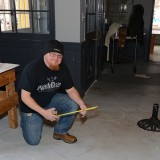 Mike Miller, co-owner of Noble Order, measures an area for a table and stools at the future brewery. (Photo by Theresa Skutt)