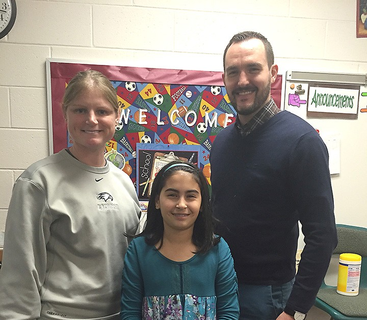 Zionsville Middle School teacher Holly Hook, left, is the January Teacher of the Month. She was nominated by student Mia Wilhite, middle, and she received a gift card from Jason Riley of Market District. (Photo by Anna Skinner)