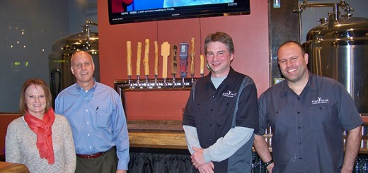 Fishers on Tap event co-chairs Michele Whelchel and Bill Jerrow join Heady Hollow Brewing Company owners George Garrison and Keefe Pietri behind the bar at the Heady Hollow tasting room. Heady Hollow is one of the newer breweries joining this winter's Fishers on Tap event. (Photo by Sam Elliott)