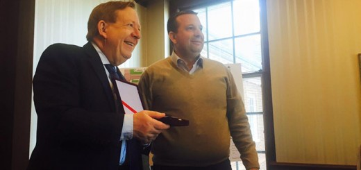Carmel Mayor Jim Brainard accepts a gift from Preterit Sinajy, mayor of Berat, Albania, during a visit of Albanian mayors to Indiana. Brainard hosted the guests at Carmel City Hall and answered questions about city redevelopment efforts. (Photo by Adam Aasen)