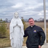 Father Brian Dudzinski with the statue of Mary, the mother of Jesus, outside St. John Vianney's current church building. (Photo by Sam Elliott)