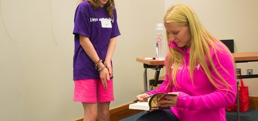 Laura Bowers watches Pippa Mann autograph a book.
