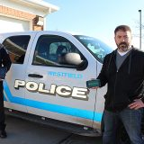 Assistant Chief Scott Jordan, left, and Aaron Sherrick work together to best notify neighborhoods about crime or city information through the mobile app, Nextdoor. (Photo by James Feichtner)