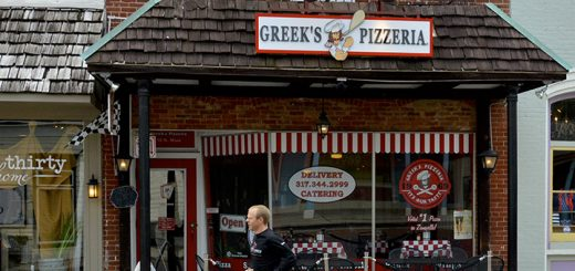 Mike Cole, owner of Greek's Pizzeria and organizer of the Zionsville Half Marathon, runs past his Main Street business, which will serve as the start and finish line for the inaugural race. (Photo by Lisa Price)