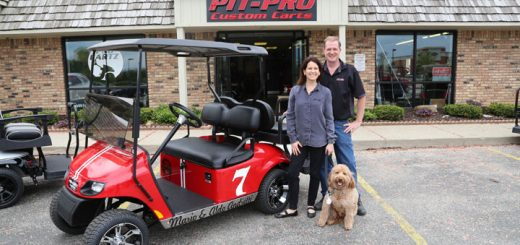 Pau and Mike Nelson and their dog, Oliver, outside of ProCartz. The Carmel company designed a custom golf cart for former racecar drivers and twins Mario and Aldo Andretti. (Photo by Ann Marie Shambaugh)