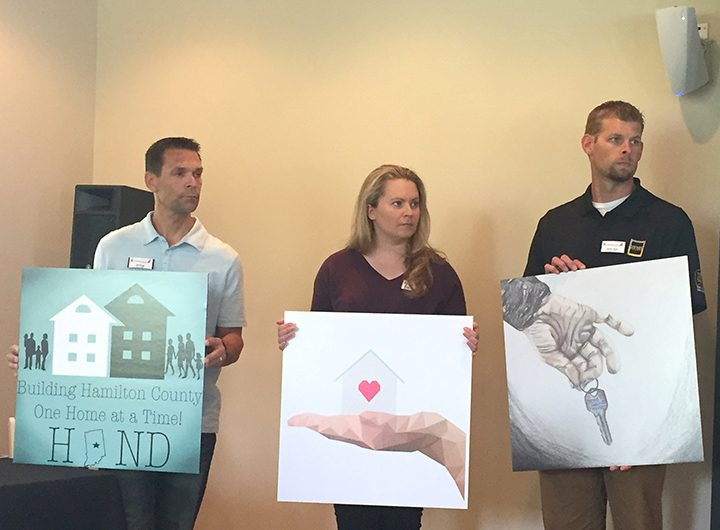 From left, Jeff Bragg of Noblesville schools, Brittany Heidenrich of American Structurepoint and Jeremy Dixon of Meyer-Najem present the winners of the HAND Student Design Challenge, their service project along with other HCLA participants. (Photo by Adam Aasen)