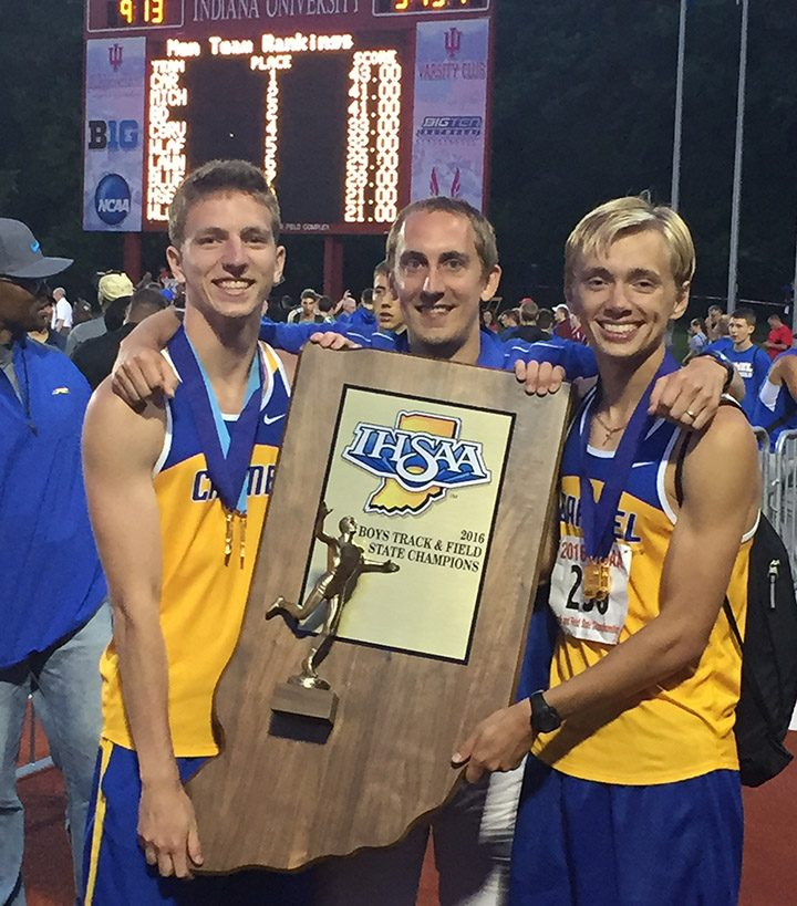 From left, Teddy Browning, coach Colin Altevogt and Ben Veatch celebrate Carmel High School's second consecutive state title for boys track. (Submitted photo)
