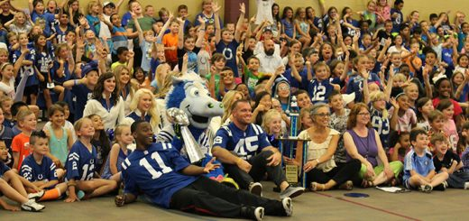 Indianapolis Colts wide receiver Quan Bray (No. 11), mascot Blue (Trey Mock) — with the 2007 Lombardi Trophy — and long snapper Matt Overton (No. 45) pose with Cumberland Road Elementary students and staff during a visit to the school May 25. (Photo by Eric Kuznar)