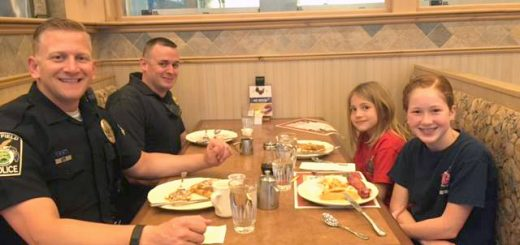 From left, Officer Adam Zosso, Officer Chuck Nichols, Elle French and Grace Miller enjoy breakfast together.
