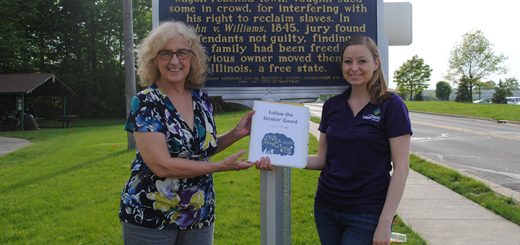 Director Cheryl Fesmire, left, and Community Events Manager Kelley Wells pause at the Rhodes Family Incident sign at Asa Bales Park. (Photo by Anna Skinner)
