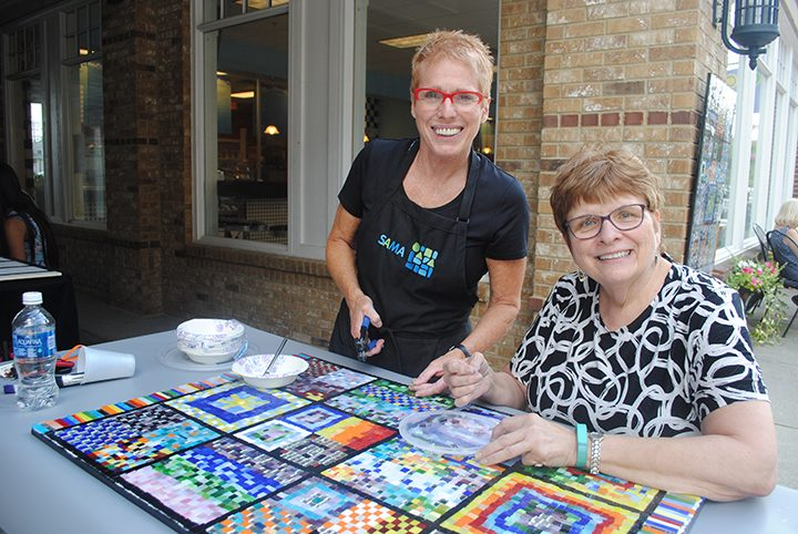 Chris Kus, right, and Nancy Keating pause by the mosaic. (Photo by Anna Skinner)