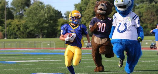 Desmond Duffy runs to the end zone with mascots Blue of the Indianapolis Colts and Staley Da Bear of the Chicago Bears in pursuit.