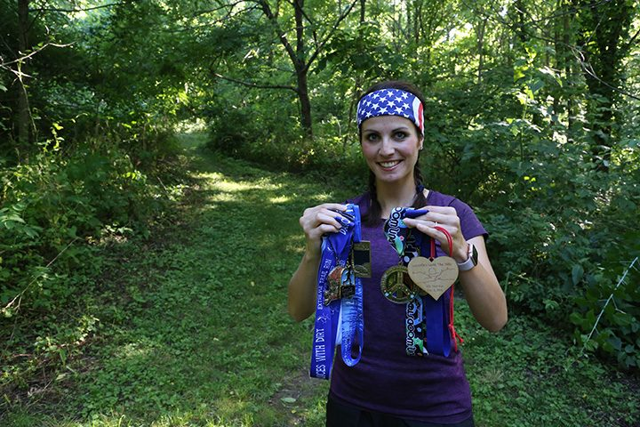 Stefanie Sharp displays medals she has accumulated during the past four years. (Photo by Ann Marie Shambaugh)