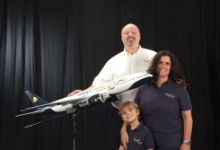 Chris Allen and his wife, Sandy, and son, Samuel, stand with a Legacy Travel Club model. (Submitted photo)