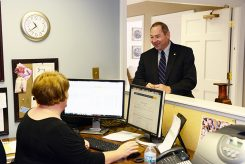Robert Cowan discusses business with administrative assistant Jowana Zehrung at F.C. Tucker in Carmel. (Photo by Theresa Skutt)