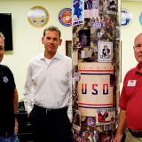 From left, Charles Ridings, Mike Hanlon and Bob Legacy converse near a pillar with advertisements for the U.S. military. Ridings is the USO of Indiana executive director and Hanlon is director of development. (Photo by Jason Conerly)