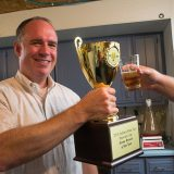 Tom Wallbank gives a toast with his trophy from the Indiana State Fair. Wallbank won the title of Indiana Homebrewer of the Year at the Indiana State Fair.(Photo by Jason Conerly)