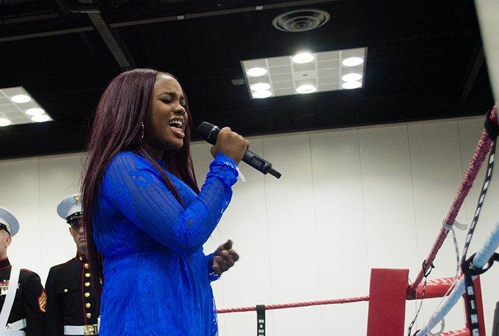 """Jamera Robinson sings in front of a crowd as Marines stand silently in the background. Robinson sang the national anthem and """"Lift Every Voice and Sing."""" (Photo by Jason Conerly)"""
