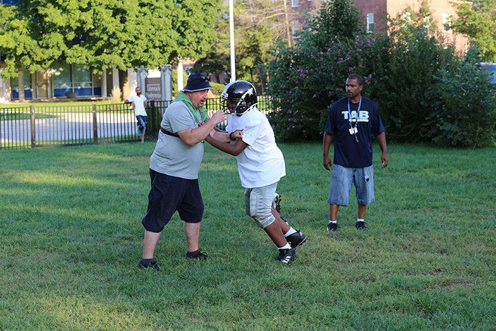 Coach Chris Metcalf works with Jeremiah Kurtz during practice.