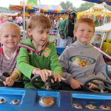 Shea Weidner, center, takes her first carnival ride at a previous VIP Carnival, with her brothers, Cruz, left, and Von by her side. (Submitted photo)