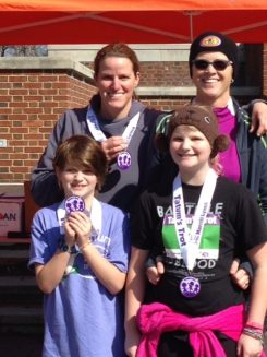 "Melanie Brown, back left, her partner, Amy Harbin, and her daughters, Tatum Brown and Ahni Brown Harbin, display their medals after the 2015 Tatum's Trot 5K. ""Everyone else in my family hates to run, so it was really cool that they did this,"" Melanie Brown said. (Submitted photos)"
