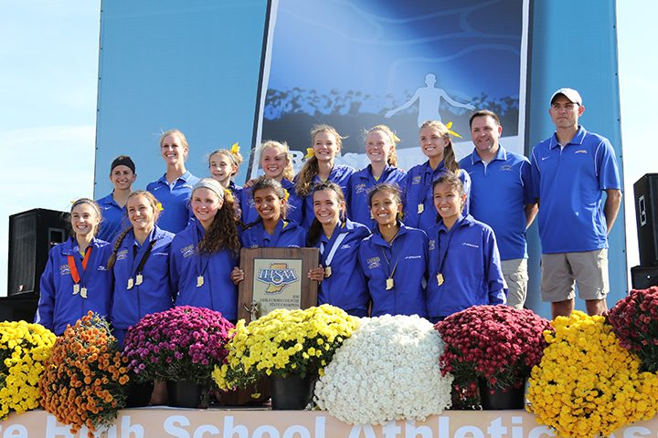 The Carmel girls cross country team holds up the state championship trophy. (Submitted photo)