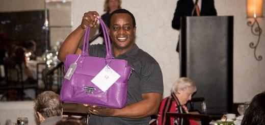 Steve Jefferson, a WTHR Channel 13 crime reporter, poses with a purple purse.