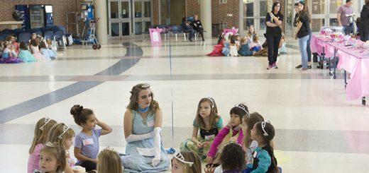 "A group of young princesses sits in a circle with their ""fairy godmother"" group leader from the Accents choir."